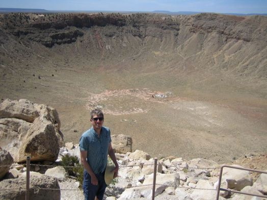 Yours truly standing next to Meteor Crater, Arizona, a hole in the ground 1.2 km across and 170 m deep (click to embiggen)